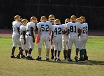 Free Stock Photo: Middle school football players in a huddle on the field.
