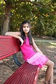 Free Stock Photo: A beautiful young girl sitting on a bench outdoors.