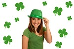 Free Stock Photo: A cute young girl dressed up for Saint Patrick's Day with a green hat surrounded by shamrocks.