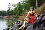 Free Stock Photo: A beautiful young woman posing in a red dress on rocks by a lake.