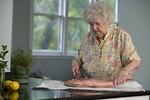 Free Stock Photo: An elderly woman preparing fresh fish.