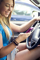 Free Stock Photo: This image depicts a teenage girl driving while attempting to text one of her friends. You can see her attention is on the phone, and not on the roadway, thereby, increasing the level of risk of being involved in a hazardous vehicular accident, not only for her, but other motor vehicle operators, and pedestrians, as well.