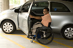 Free Stock Photo: The man pictured here had parked his automobile in a handicapped spot, then had assembled his collapsible wheelchair, and maneuvered his body into the wheelchair\'s seat. Note that this car was equipped with a steering wheel-located manual braking and acceleration knob.