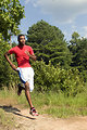 Free Stock Photo: This young man was taking a jog through a Georgia recreational park on a sunny day. He was wearing a red, skin-tight shirt, and bright white shorts, both of which reflected the sun\'s harmful rays, and kept him cool as he completed his run. His running shoes were especially designed for this kind of activity, affording the needed support, and comfort to his feet.