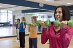 Free Stock Photo: A group of women participating in an instructor lead aerobics exercise session, which at this point, included the use of light-weight dumbbells that these class attendees were using in their attempt to build upper body strength.