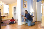 Free Stock Photo: While this African-American father was in the process of repairing an interior door frame inside his residence, his young son was playing with a toy car in an adjacent room.