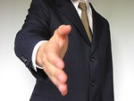 Free Stock Photo: Business man in a blue suit extending his hand for a handshake.
