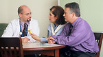 Free Stock Photo: A Hispanic doctor and Caucasian couple (male and female) are seated around a table talking.