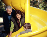 Free Stock Photo: A Caucasian family group enjoying an outing in a playground with a young male child.