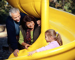 Free Stock Photo: A Caucasian family group enjoying an outing in a playground with a young girl.