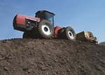 Free Stock Photo: A tractor moving topsoil on a hill.
