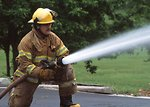 Free Stock Photo: A Redings Mill, Missouri, firefighter sprays water pumped from a portable tank filled with water from a dry hydrant. Dry hydrants and portable tanks greatly improve fire fighting capabilities in rural areas.