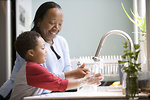Free Stock Photo: This African-American mother was shown in the process of teaching her young son how to properly wash his hands at their kitchen sink, briskly rubbing his soapy hands together under fresh running tap water.