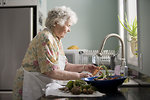 Free Stock Photo: An elderly woman properly cleaning carrots and radishes. .