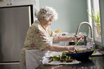 Free Stock Photo: An elderly woman cleaning a number of carrots and radishes. .