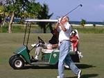 Free Stock Photo: A man swinging a golf club while standing next to a golf cart.