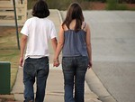 Free Stock Photo: Teen boy and girl holding hands walking on down the street.