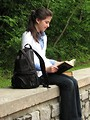 Free Stock Photo: A young schoolgirl reading a book on a stone wall outside.