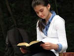 Free Stock Photo: A young schoolgirl reading a book outside.