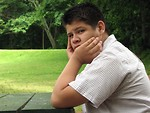 Free Stock Photo: A teen latino boy sitting at an outdoor table looking worried.