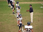 Free Stock Photo: A high school football team lined up before a game with their coach.