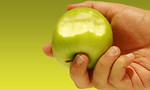 Free Stock Photo: A hand holding a bitten green apple.