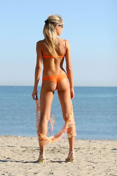 A girl in an orange bikini standing on the beach.