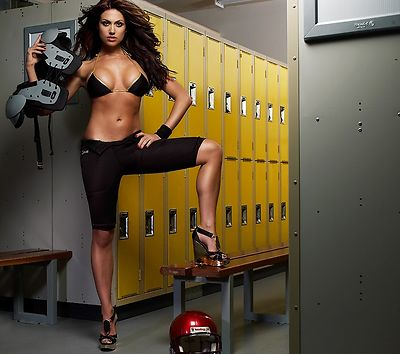 A beautiful girl in a bikini top in a locker room with football gear.
