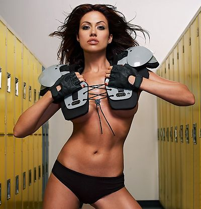A beautiful woman posing with football gear in a locker room.