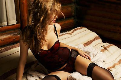 A beautiful woman posing in lingerie on a bed in a log cabin.