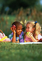Free Stock Photo: Young children eating apples while having a picnic on the grass.