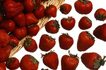 Free Stock Photo: A basket full of strawberries spilling on a white background
