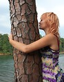 Free Stock Photo: A beautiful young woman hugging and kissing a tree by a lake