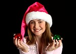 Free Stock Photo: A beautiful young girl in a pink santa hat holding Christmas tree ornaments
