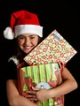 Free Stock Photo: A cute young girl in a Santa hat holding a bag of presents