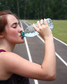 Free Stock Photo: A cute young girl drinking water on a track field.