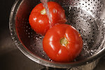 Free Stock Photo: Two fresh tomatoes being washed under running water