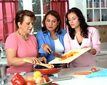 Free Stock Photo: A Hispanic family with three adult females are in the kitchen preparing healthy food.