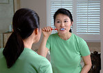 Free Stock Photo: An Asian woman brushes her teeth while looking in a mirror.