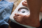 Free Stock Photo: Shown is a close-up of the feet of a man standing on a bathroom scale with a towel lying nearby.