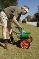 Free Stock Photo: This man was pictured bent over, filling his fertilizer dispenser with fertilizer granules, which he was about to spread over his newly-mowed lawn.