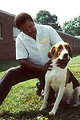 Free Stock Photo: Pictured is a handler, kneeling, wearing a white lab shirt. He is holding a fox hound.