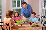 Free Stock Photo: A Caucasian family sits for lunch. The adult female serves a salad as two children (male and female) and an adult male look on.