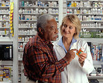 Free Stock Photo: An older African-American man talks to a Caucasian female pharmacist as she explains his prescription.