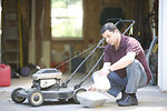 Free Stock Photo: This man was in the process of changing his lawnmower\'s oil. .