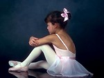 Free Stock Photo: A young ballerina posing on the floor with a dark background