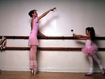 Free Stock Photo: Two ballerinas in pink practicing on a barre with a rose