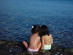 Free Stock Photo: Two young girls sitting on the beach by the water