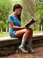 Free Stock Photo: A beautiful African American teen girl reading a book on a stone wall outside