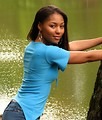 Free Stock Photo: A beautiful African American teen girl posing against a tree near a lake